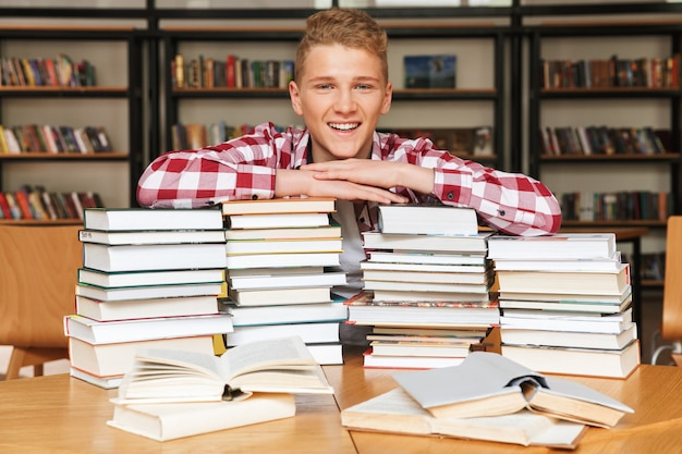 Lächelnder teenager, der am bibliothekstisch sitzt