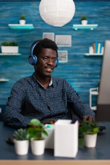 Lächelnder teenager, der kopfhörer trägt, hört musik, während er marketingideen für die geschäftsleason mit der e-learning-plattform eingibt. schüler sitzen am schreibtisch und genießen ihre freizeit während der online-bildung