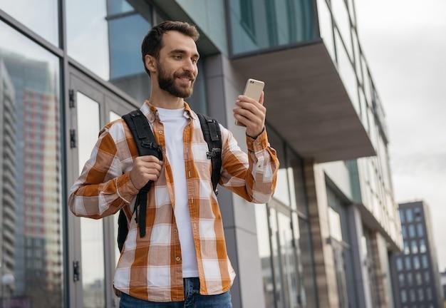 Lächelnder tourist mit rucksack, der smartphone hält und besten weg mit navigationskarte sucht