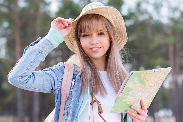 Lächelnder tragender hut des jungen weiblichen reisenden, der in der hand karte hält