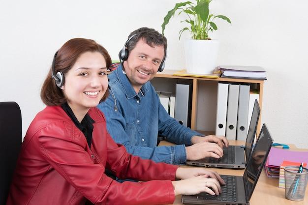 Lächelnder tragender kopfhörer des weiblichen und männlichen kundendienstmitarbeiters mit den kollegen, die im hintergrund im büro arbeiten
