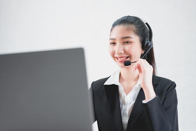 Lächelnder tragender mikrofonkopfhörer des asiatinberaters des kundenbetreuungstelefonbetreibers am arbeitsplatz.