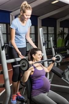 Lächelnder trainer, der anhebendem barbell der schwangeren frau an der turnhalle hilft