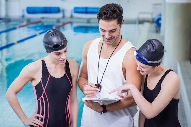 Lächelnder trainer, der klemmbrett an den schwimmern in der freizeitmitte zeigt