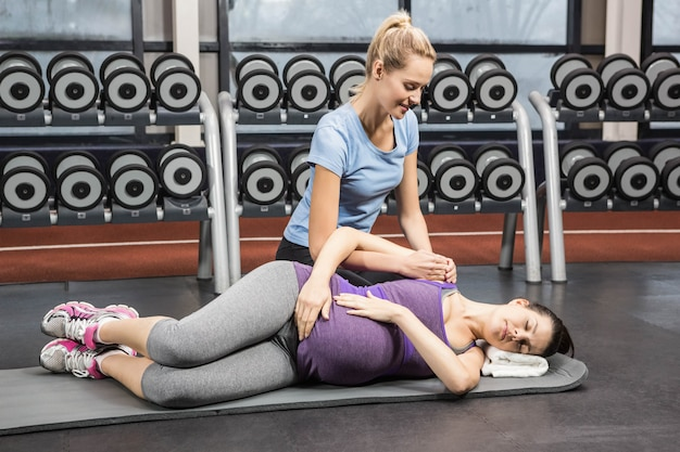 Lächelnder trainer, der schwangere frau an der turnhalle manipuliert