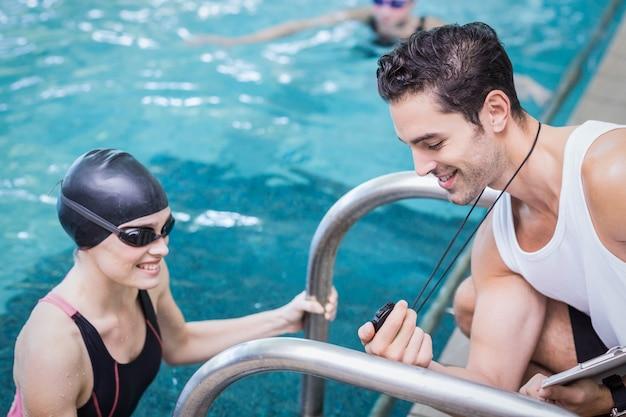 Lächelnder trainer, der stoppuhr am schwimmer in der freizeitmitte zeigt