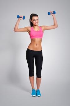 Lächelnder trainer des fitnesstrainings mit hanteln