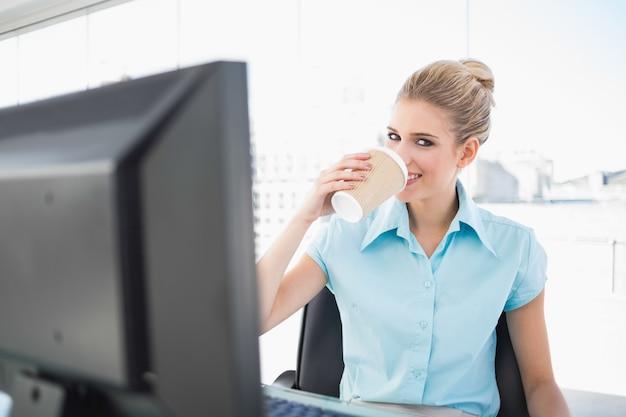 Lächelnder trinkender kaffee der eleganten geschäftsfrau