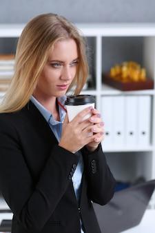 Lächelnder trinkender kaffee der geschäftsfrau von einer papierschale im büroporträt