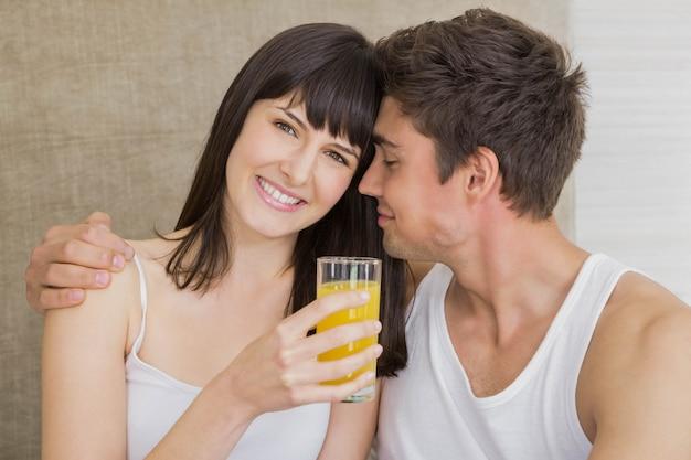 Lächelnder trinkender saft der frau während mann, der auf bett im schlafzimmer umfasst
