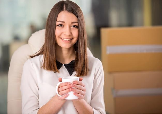 Lächelnder trinkender tee der jungen geschäftsfrau im büro.