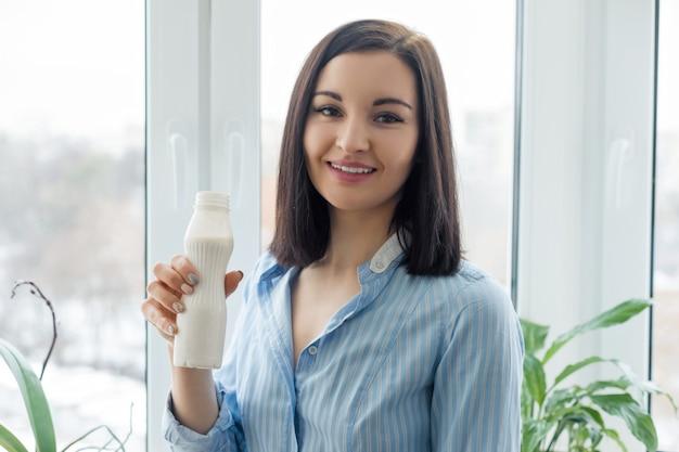 Lächelnder trinkmilchgetränkjoghurt der frau von der flasche