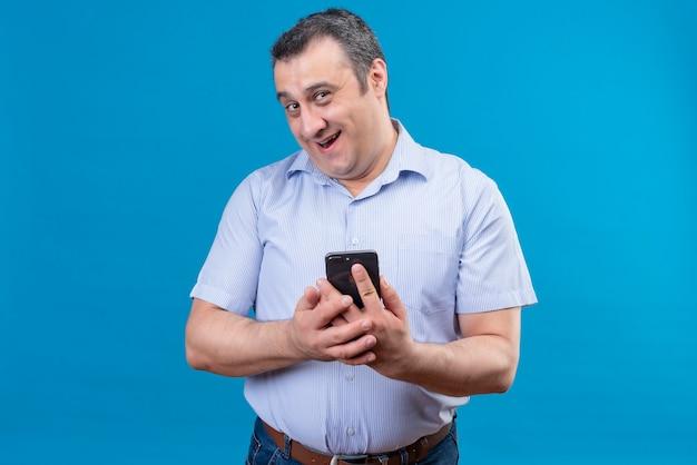 Lächelnder und freudiger mann im blau gestreiften hemd, der sein handy auf einem blauen hintergrund hält