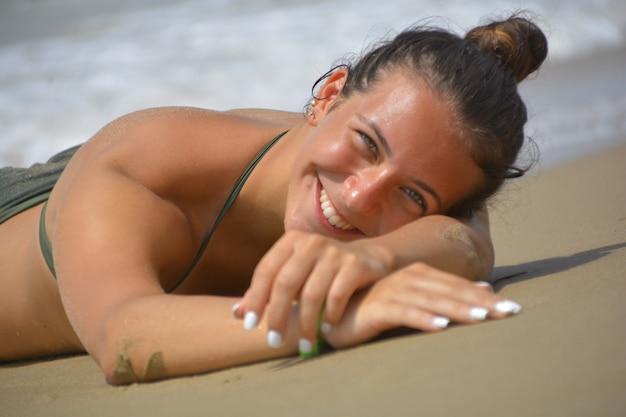Lächelnder und glücklicher teenager im bikini, der am meer liegt