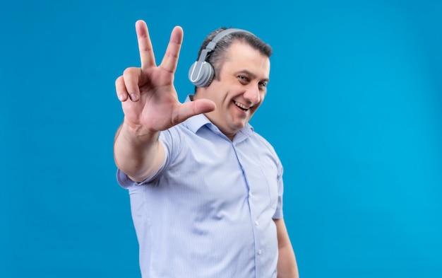 Lächelnder und positiver mann mittleren alters im blau gestreiften hemd in den kopfhörern, die mit den fingern nummer sechs auf einem blauen hintergrund zeigen