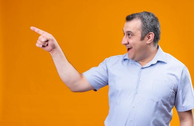 Lächelnder und positiver mann mittleren alters im blauen vertikalen gestreiften hemd, das mit zeigefinger auf die obere rechte ecke zeigt, während er auf einem orangefarbenen hintergrund steht