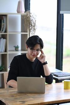 Lächelnder unternehmer des jungen mannes, der online mit laptop-computer arbeitet.