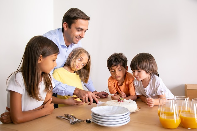 Lächelnder vater, der leckeren geburtstagskuchen für kinder schneidet. schöne kleine kinder, die in der nähe des tisches stehen, gemeinsam geburtstag feiern und auf nachtisch warten. kindheits-, feier- und feiertagskonzept
