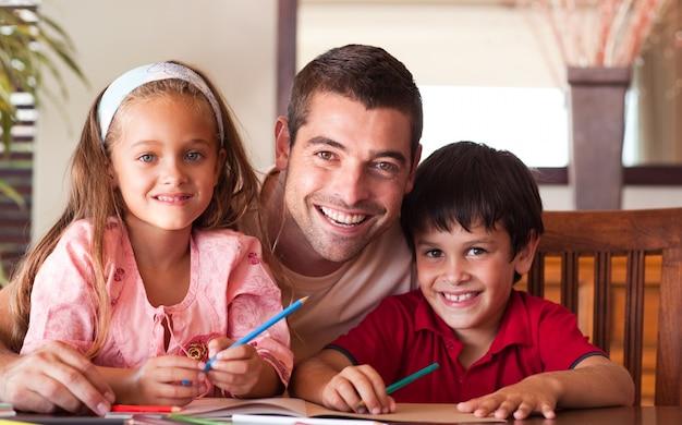 Lächelnder vater, der seinen kindern für hausarbeit hilft