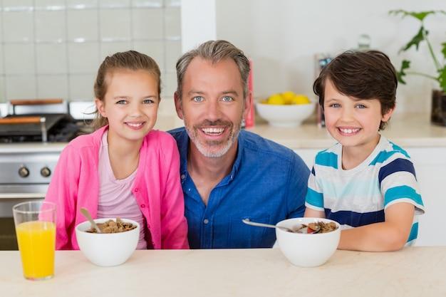 Lächelnder vater und kinder, die frühstück in der küche haben