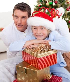 Lächelnder vater und sein sohn, die weihnachtsgeschenke halten