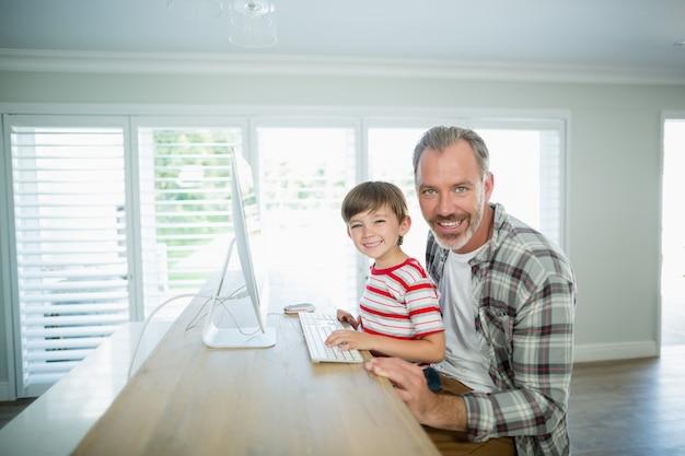 Lächelnder vater und sohn, die zu hause am computer arbeiten