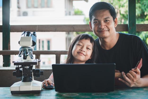 Lächelnder vater und tochter lernen von zu hause mit laptop und mikroskop. coronavirus oder covid-19 outbreak schulschließungen
