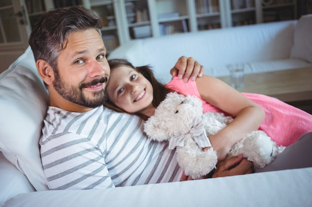 Lächelnder vater und tochter sitzen auf sofa mit einem teddybär