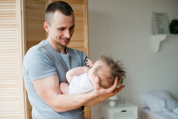 Lächelnder vati, der baby auf händen hält