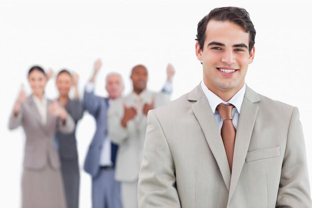 Lächelnder verkäufer mit zujubelndem team hinter ihm