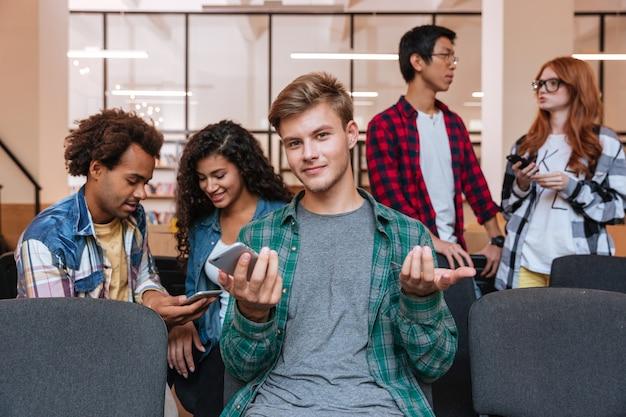 Lächelnder verwirrter junger mann, der handy sitzt und benutzt, während seine freunde sprechen