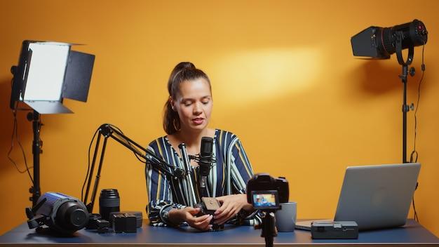 Lächelnder videografie-experte, der der kamera zeigt, wie die flüssigkeitskopfplatte montiert werden kann. influencer, der online-internetinhalte über videogeräte für web-abonnenten und -vertrieb erstellt, digitale vlog-gespräche