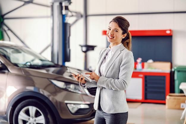Lächelnder weiblicher autoverkäufer, der in der garage des autosalons steht und tablette verwendet.