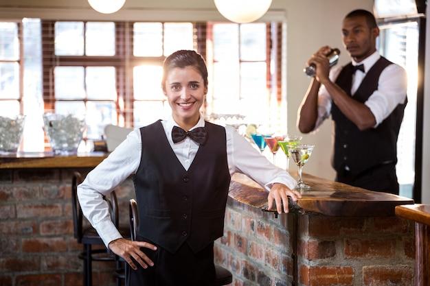 Lächelnder weiblicher barkeeper, der am bartheke steht