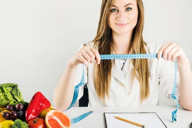 Lächelnder weiblicher diätetiker, der messendes band mit gesundem lebensmittel auf schreibtisch hält