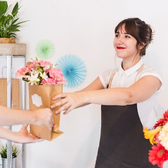 Lächelnder weiblicher florist, der ihrem kunden blumenpapiertüte gibt