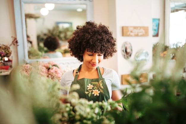 Lächelnder weiblicher florist, der im blumenshop steht