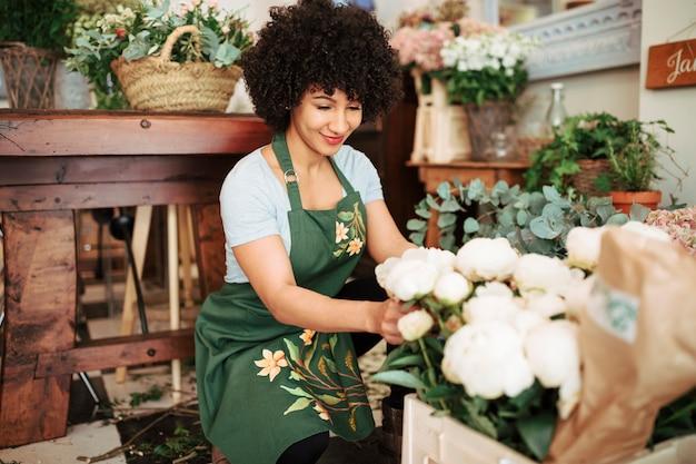 Lächelnder weiblicher florist, der weiße pfingstrosenblumen vereinbart