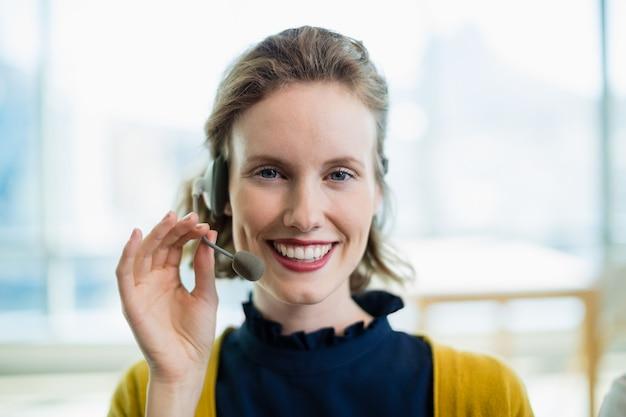 Lächelnder weiblicher geschäftsleiter mit headset, der im büro sitzt