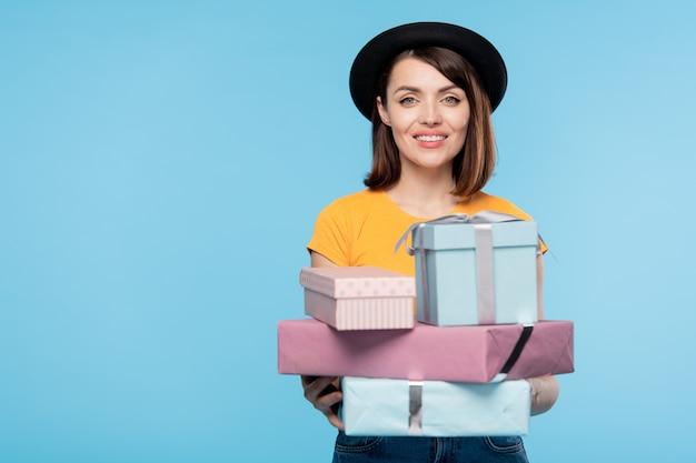 Lächelnder weiblicher käufer mit stapel verpackter geschenke für feiertagsstand