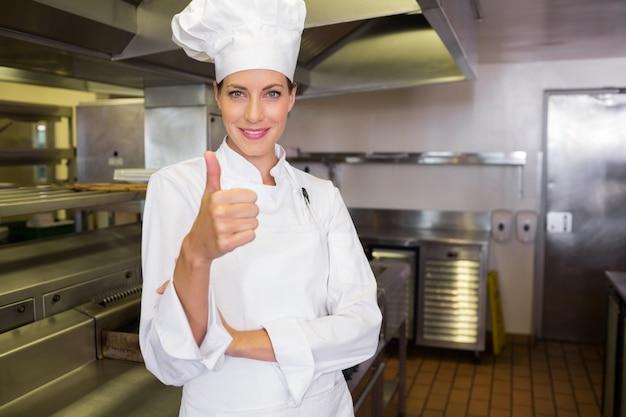 Lächelnder weiblicher koch, der daumen oben in der küche gestikuliert