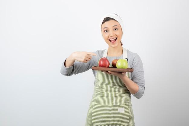 Lächelnder weiblicher koch, der teller mit äpfeln auf weiß hält.