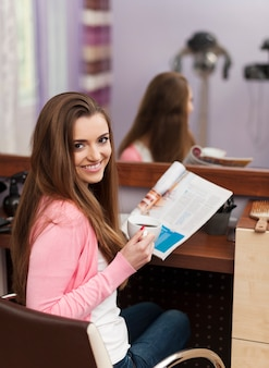 Lächelnder weiblicher kunde, der im friseursalon sitzt
