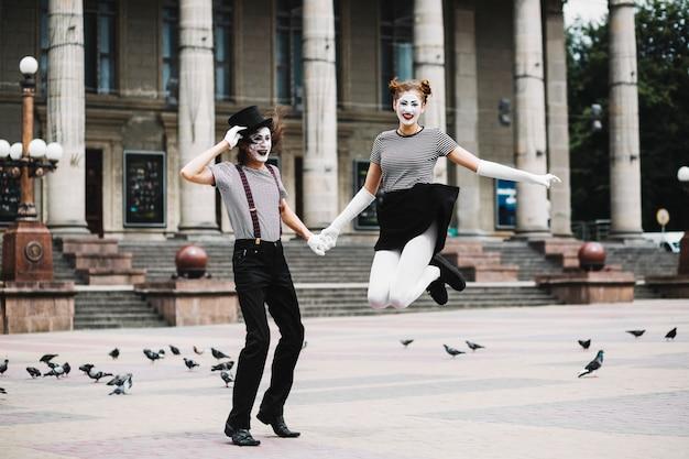 Lächelnder weiblicher pantomime, der die hand des männlichen pantomimen hält, die vor gebäude springt