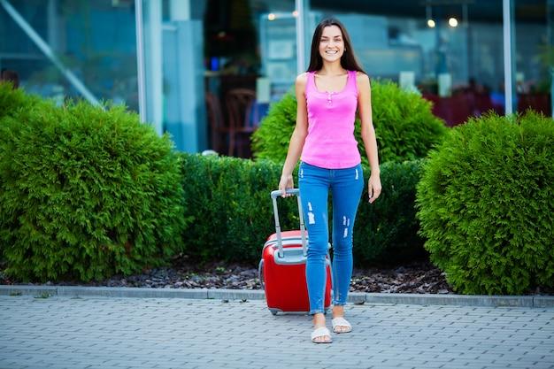 Lächelnder weiblicher passagier, der koffer durch flughafen zieht