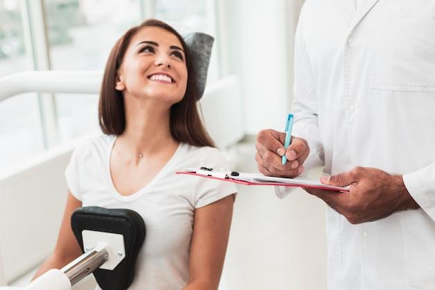 Lächelnder weiblicher patient, der doktor betrachtet