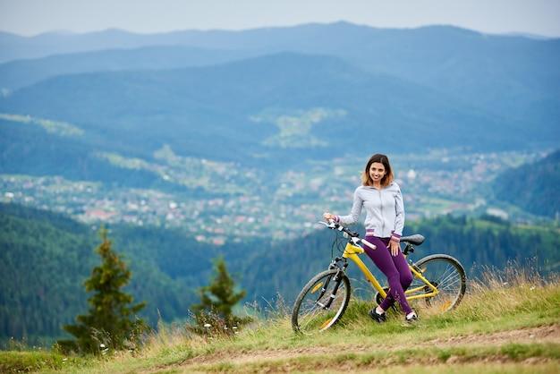 Lächelnder weiblicher radfahrer, der auf gelber mountainbike nahe einer ländlichen spur sich entspannt.