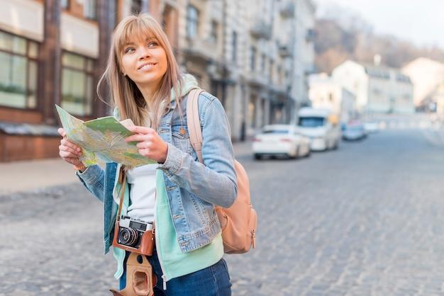 Lächelnder weiblicher reisender, der auf hintergrund der städtischen landschaft mit karte steht