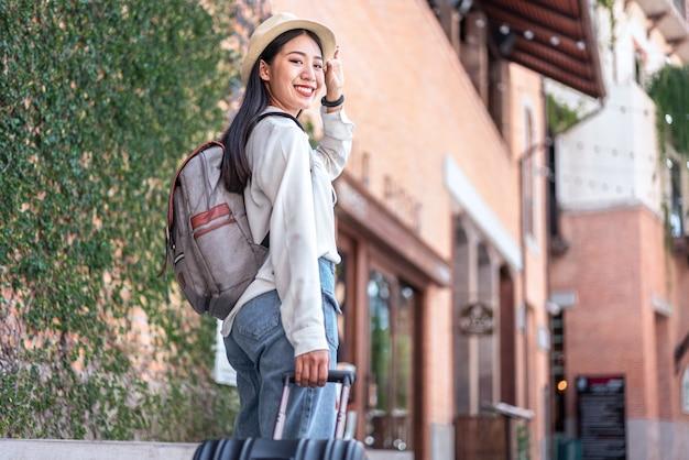 Lächelnder weiblicher reisender, der schwarzen koffergepäcktasche schleppend zu fuß zum passagiereinsteigen in flughafen, reisekonzept schleppt.