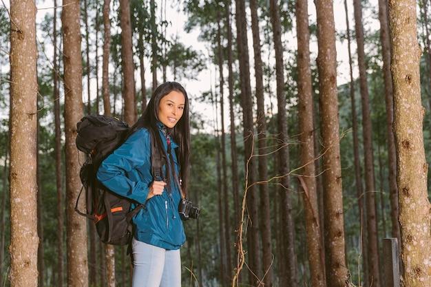 Lächelnder weiblicher reisender mit rucksack und kamera